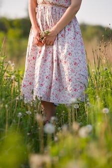Dziewczyna w pięknej sukience z kwiatami w dłoniach spaceruje po zielonym polu w słoneczny letni dzień