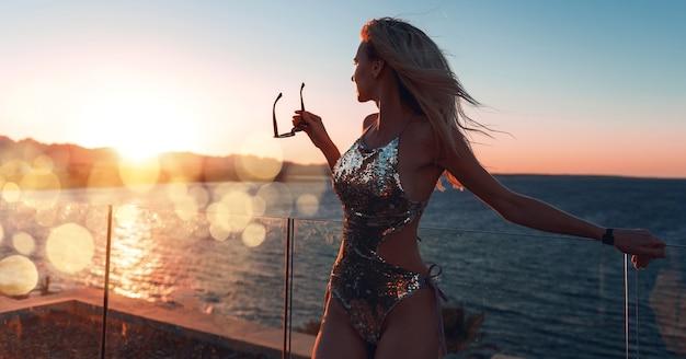 Dziewczyna w pięknym kostiumie kąpielowym o zachodzie słońca nad morzem, trzymająca okulary przeciwsłoneczne