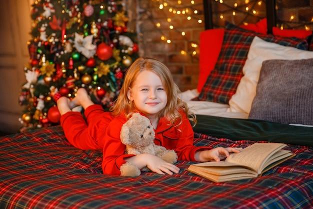 Dziewczyna w piżamie, leżąc na łóżku przytulanie misia