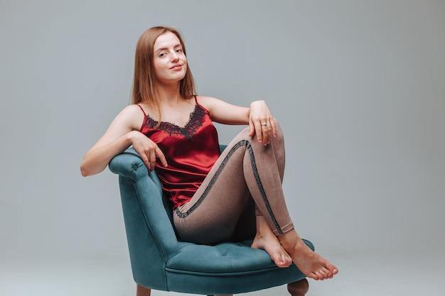 Dziewczyna w piżamie siedzi na krześle na szarym tle