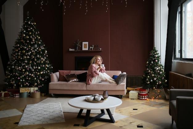 Dziewczyna w piżamie z filiżanką kawy siedzi na łóżku przy drzewie i kominku w ciemnym wnętrzu