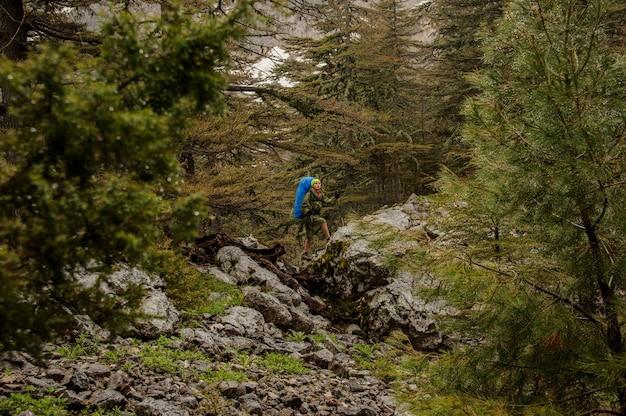 Dziewczyna w płaszczu chodzenie po skałach z plecakiem i laskami