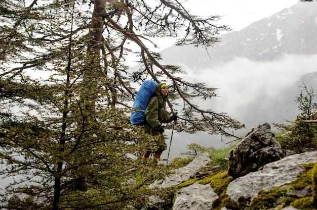 Dziewczyna w płaszczu chodzenie po skałach z plecakiem i laski