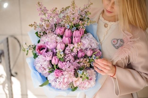 Dziewczyna w płaszczu, patrząc na bukiet fioletowych fioletowych tulipanów i bzu