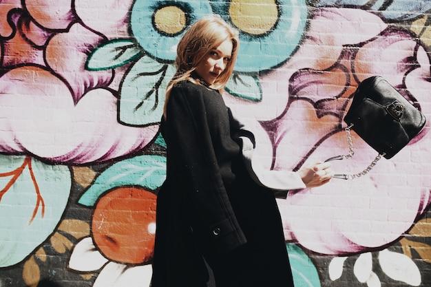 Dziewczyna w płaszczu stawia przed murem z uliczną sztuką gdzieś w nowym jorku