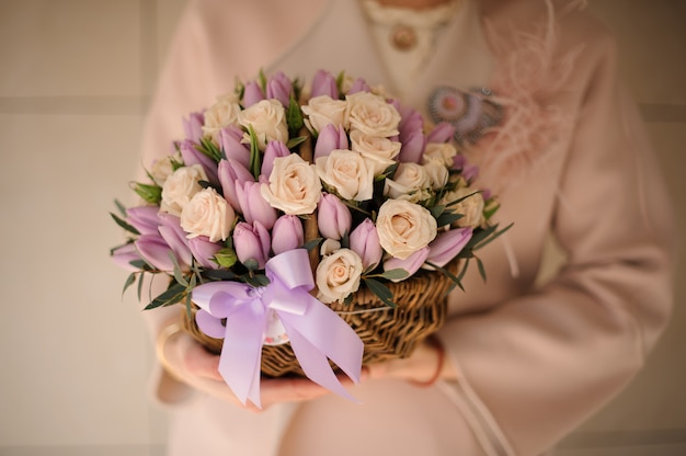 Dziewczyna w płaszczu z wiklinowym koszykiem z delikatnymi kremowymi różami i fioletowymi tulipanami