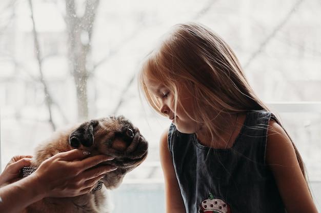 Dziewczyna w pobliżu okna ze swoim ulubionym psem, wygoda w domu, komunikacja ze zwierzakiem