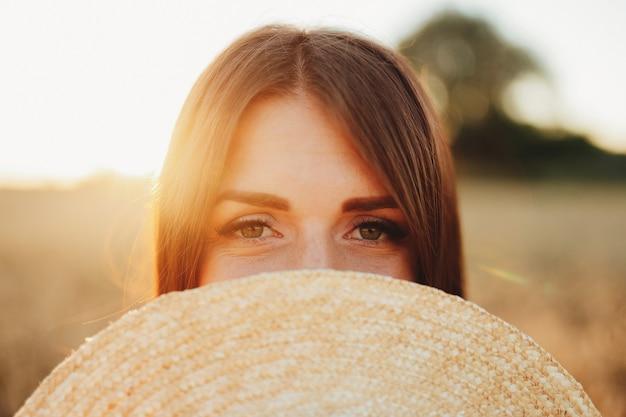 Dziewczyna w polu pszenicy, dłoń dziewczyny i kłoska pszenicy, zachód słońca na polu. wysokiej jakości zdjęcie