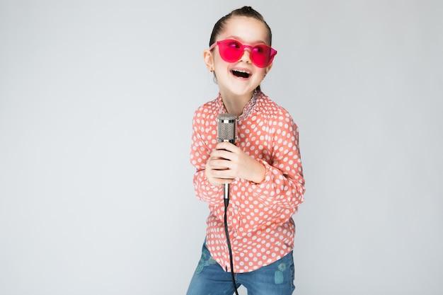 Dziewczyna w pomarańczowej koszuli, okularach i dżinsach na szarym tle.