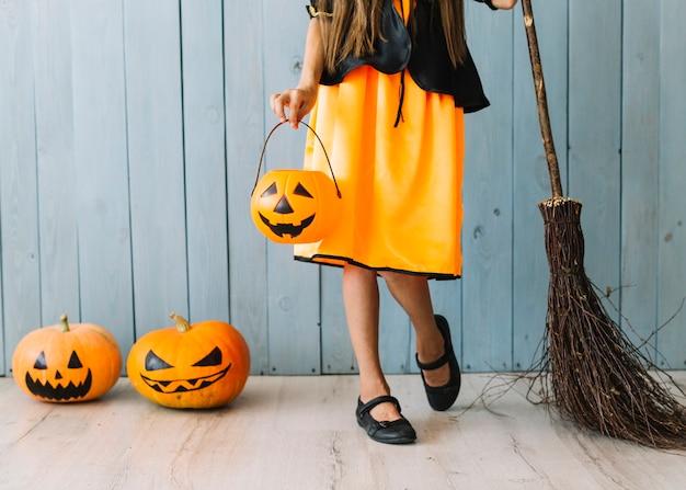 Dziewczyna w pomarańczowy i czarny strój stojący z koszem halloween i miotły