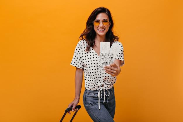 Dziewczyna w pomarańczowych okularach posiada bilety i walizkę. ciemnowłosa dorosła kobieta w kraciastej koszuli pozuje i uśmiecha się na na białym tle.