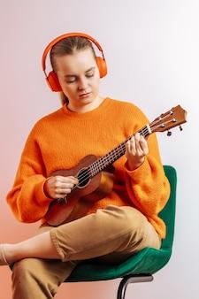 Dziewczyna w pomarańczowym swetrze i słuchawkach gra na ukulele na jasnym tle