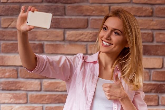 Dziewczyna w przypadkowych ubraniach pozuje, uśmiecha się i robi selfie.