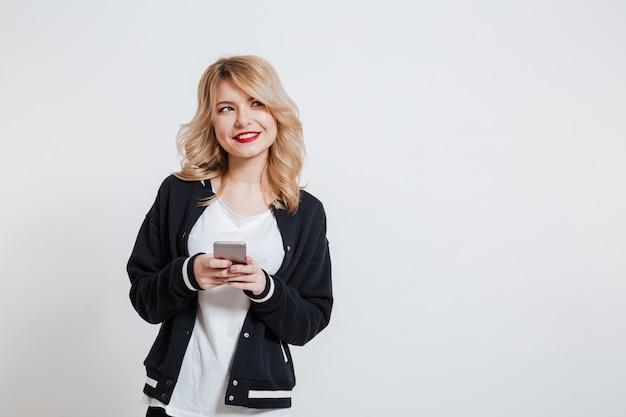 Dziewczyna w przypadkowych ubraniach trzyma telefon komórkowego i patrzeje daleko od