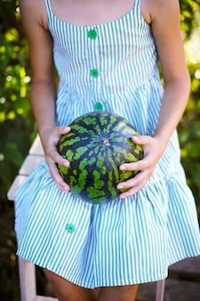 Dziewczyna w przyrodzie w pasiastej sukience siedzi i trzyma w dłoniach cały piękny dojrzały arbuz ze świeżych zbiorów bez twarzy
