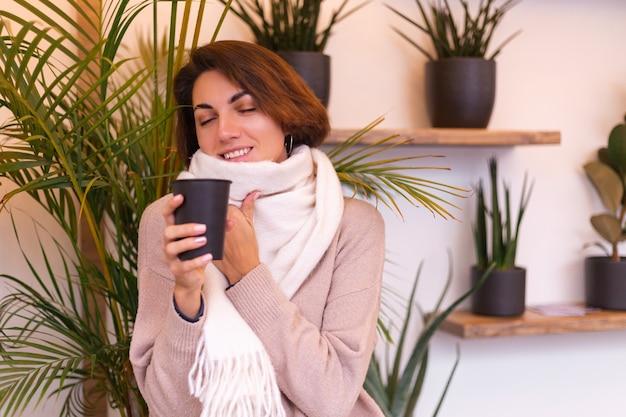 Dziewczyna w przytulnej kawiarni ogrzewa się filiżanką gorącej kawy