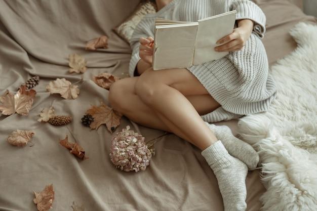 Dziewczyna w przytulnym swetrze z dzianiny i ciepłych skarpetkach leży w łóżku z książką wśród jesiennych liści.