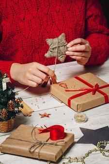 Dziewczyna w przytulnym swetrze z dzianiny ozdobionej świątecznym pudełkiem