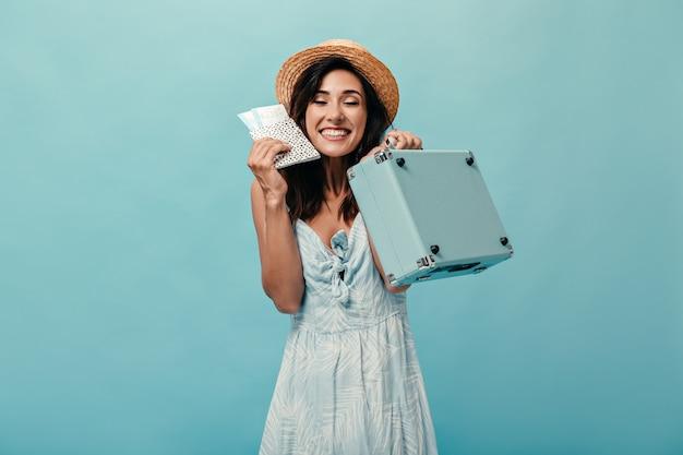 Dziewczyna w radosnym nastroju trzyma bilety wakacyjne i niebieską walizkę. kobieta w słomkowym kapeluszu z uśmiechem na twarzy, pozowanie na na białym tle.