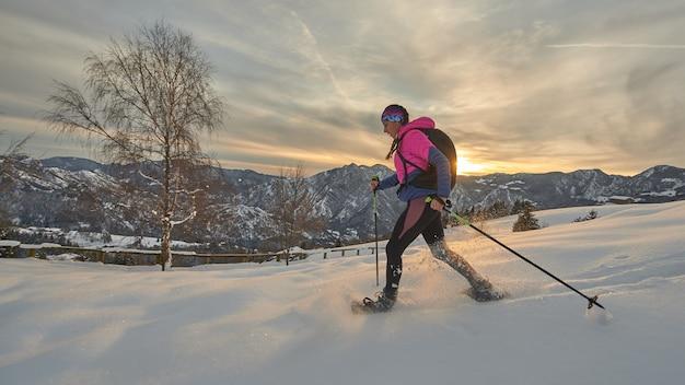 Dziewczyna w rakietach śnieżnych w piękny zimowy zachód słońca