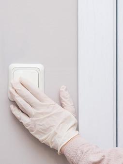 Dziewczyna w rękawiczkach medycznych włącza lub wyłącza światła w miejscu publicznym. switch, zbiór wirusów i drobnoustrojów.
