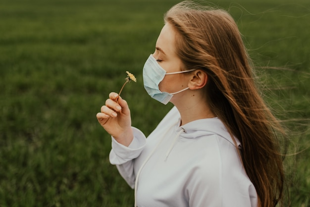 Dziewczyna w respiratorze wącha żółty mniszek lekarski. młoda blond europejska kobieta w masce ochronnej na zewnątrz.