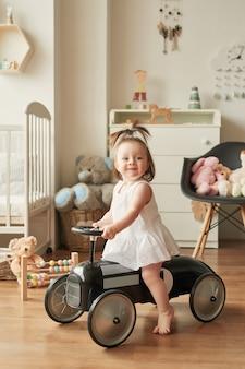Dziewczyna w retro samochodzie w pokoju dziecięcym