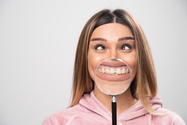 Dziewczyna w różowej bluzce wkłada lupę do ust