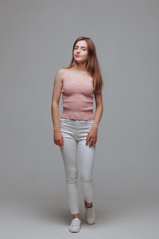 Dziewczyna w różowej koszulce i białych spodniach na szarym tle
