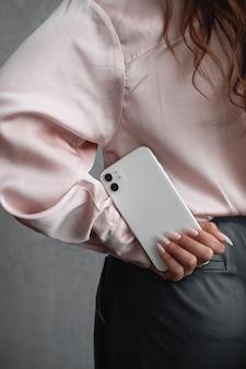 Dziewczyna w różowej koszuli i ciemnych spodniach trzyma w dłoni za plecami smartfon. młoda kobieta używa telefonu komórkowego. strzał studio. technologie. nowoczesny, swobodny styl. biznesmenka
