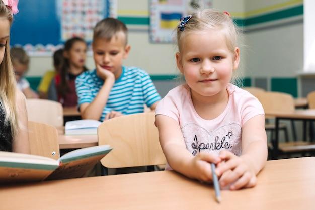 Dziewczyna w różowej koszuli siedzi przy stole