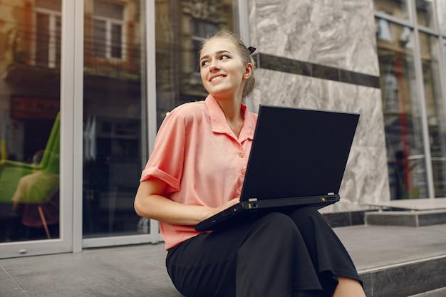Dziewczyna w różowej koszuli siedzi w pobliżu domu i korzysta z laptopa