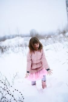 Dziewczyna w różowej kurtce delikatnie marznąca gra na zewnątrz w zimie, śnieg, pojęcie emocji