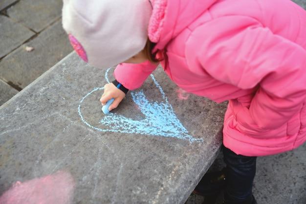 Dziewczyna w różowej kurtce rysuje kredkami serca na dużej betonowej ławce