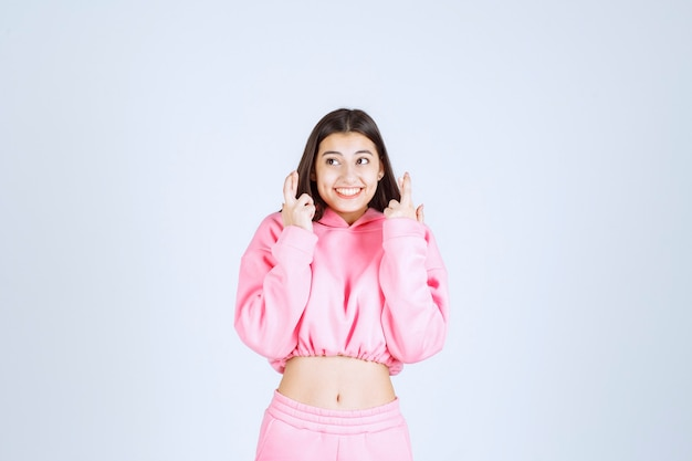 Dziewczyna w różowej piżamie czuje się szczęśliwa i pokazuje pozytywny znak ręki.
