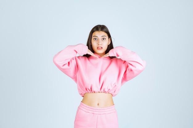 Dziewczyna w różowej piżamie daje paskudne i wesołe pozy