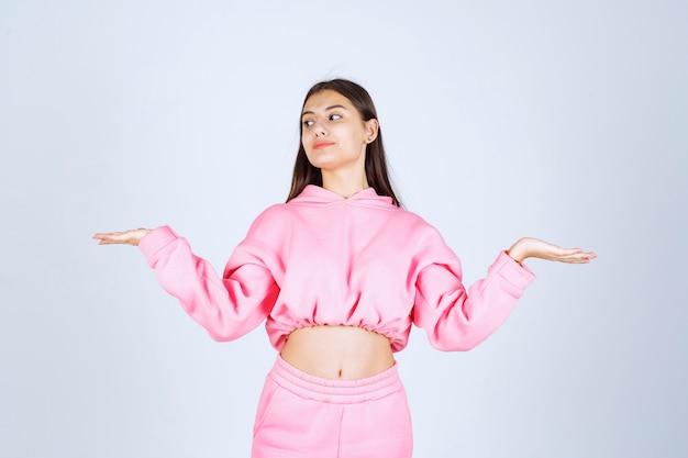Dziewczyna w różowej piżamie daje radosne i uwodzicielskie pozy