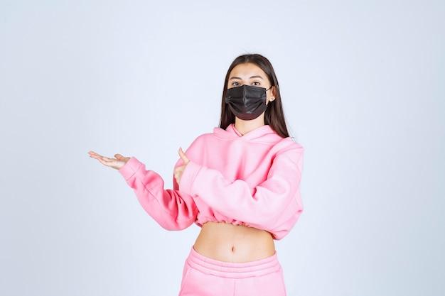 Dziewczyna w różowej piżamie i czarnej masce wskazującej lewą stronę.