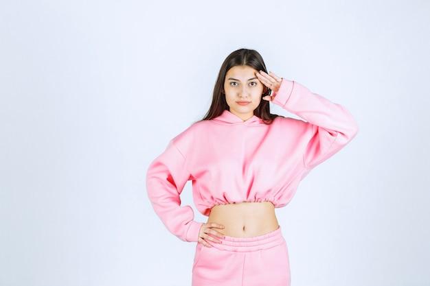 Dziewczyna w różowej piżamie kładzie palce na czole