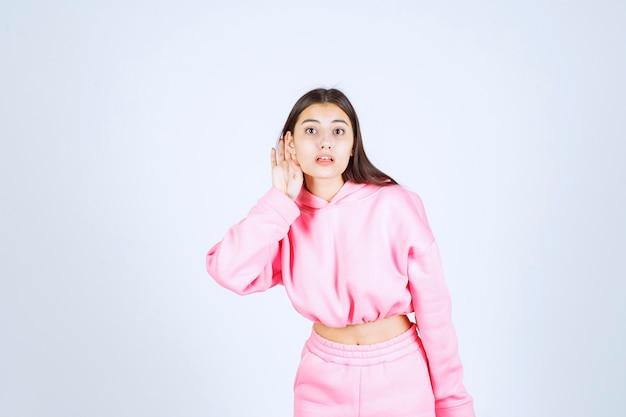 Dziewczyna w różowej piżamie ma kłopoty z głośnym głosem