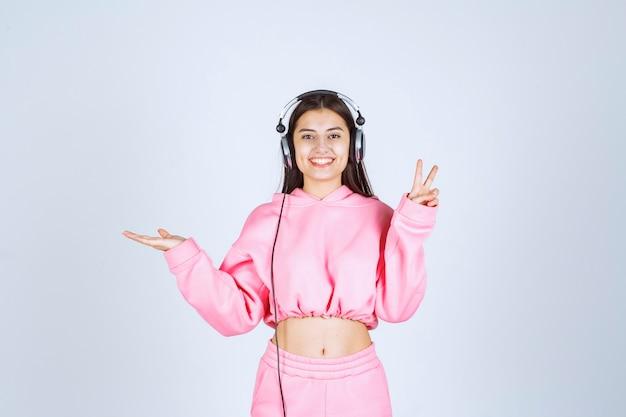 Dziewczyna w różowej piżamie, noszenie słuchawek i pokazując znak radości. wysokiej jakości zdjęcie