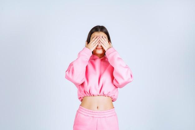 Dziewczyna w różowej piżamie patrząc przez palce