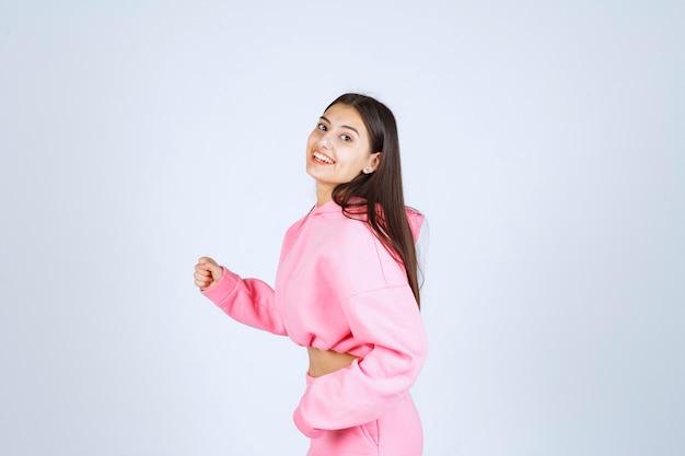 Dziewczyna w różowej piżamie pokazując mięśnie ramion
