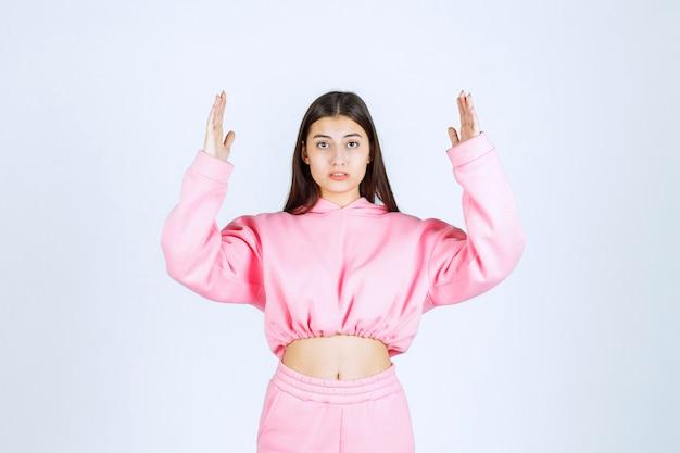 Dziewczyna w różowej piżamie pokazująca szacunkową ilość lub rozmiar produktu