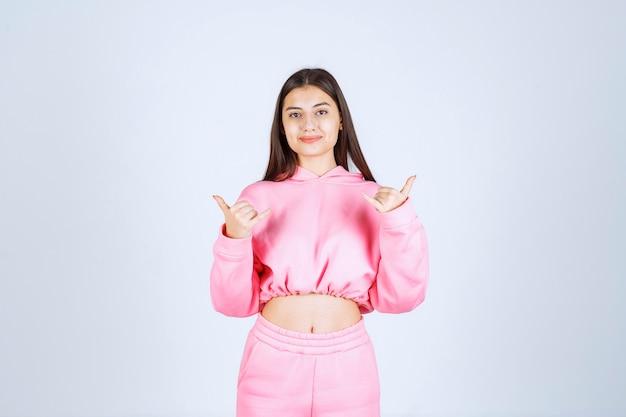 Dziewczyna w różowej piżamie pokazuje kciuk w górę