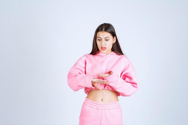Dziewczyna w różowej piżamie przedstawiającej wielkość przedmiotu