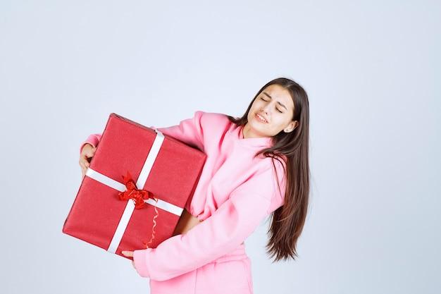 Dziewczyna w różowej piżamie przytula duże czerwone pudełko i uśmiecha się.