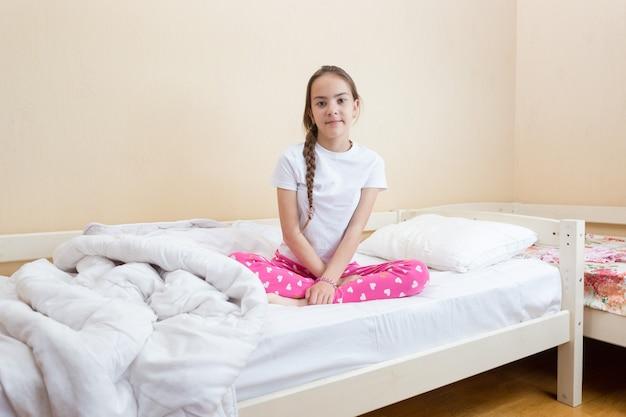 Dziewczyna w różowej piżamie siedzi na łóżku z białą pościelą i kocem