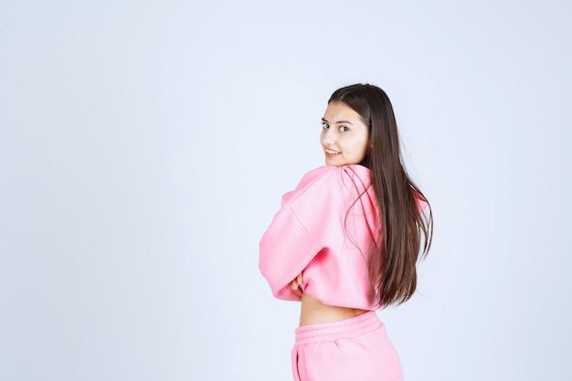 Dziewczyna w różowej piżamie skrzyżowaniu ramion i uśmiechnięta.