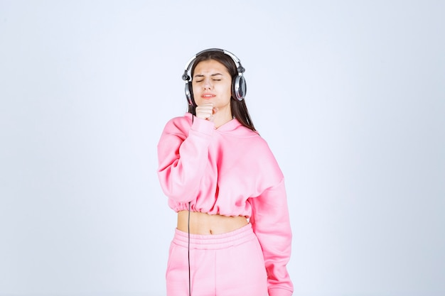 Dziewczyna w różowej piżamie słucha słuchawek i nie lubi muzyki. wysokiej jakości zdjęcie